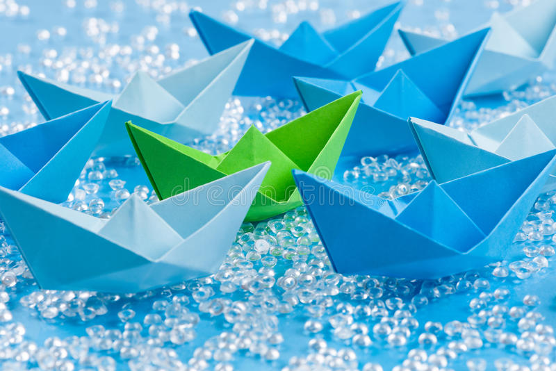 Green peace: Fleet of blue Origami paper ships on blue water like background surrounding a green one royalty free stock photos