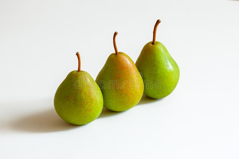 3 green pears in a row, studio shot on a white background. 3 ripe green pears on a white background one after another, studio shooting stock photography