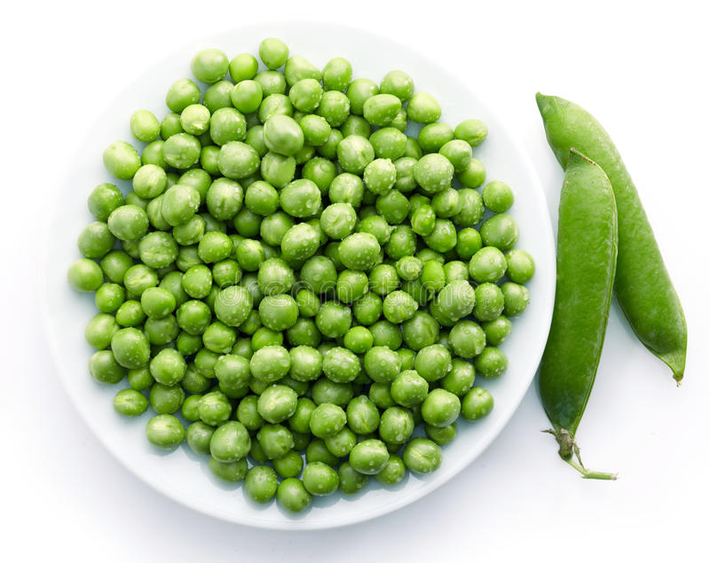 Green peas. Fresh green peas on white plate royalty free stock image