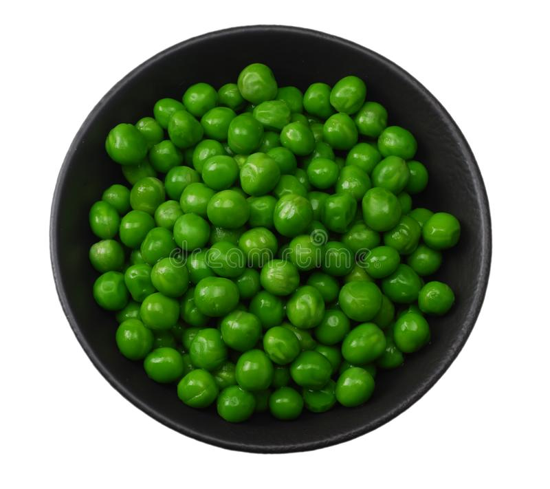 Green peas in black bowl isolated on white background. top view stock photo