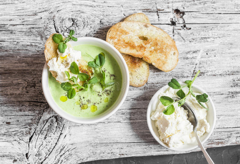 Green peas cream soup and cheese toast on the light wooden table royalty free stock photo