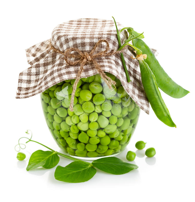 Green peas in glass jar. On white background stock image