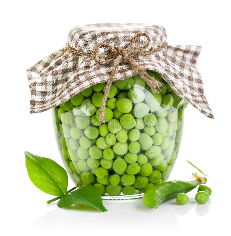 Green peas in glass jar. On white background royalty free stock images