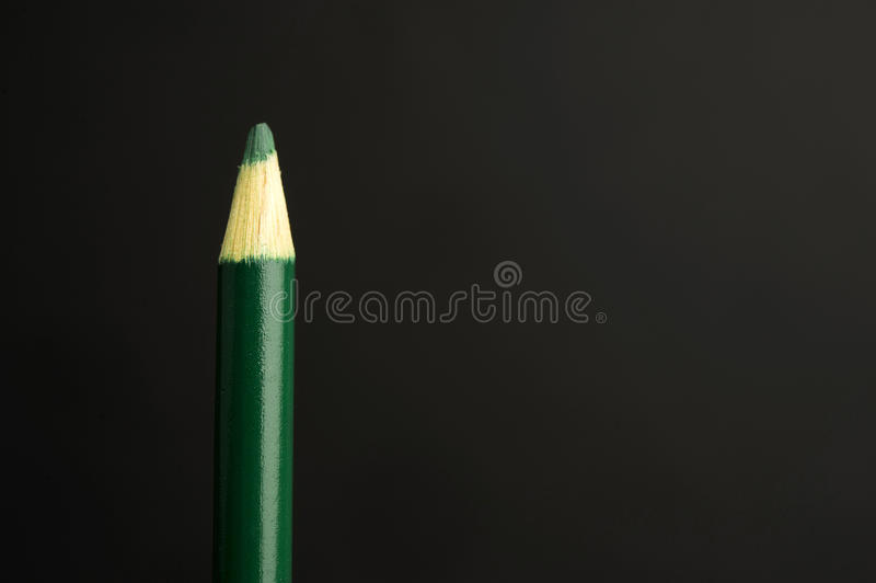 Green pencil crayon on a black background royalty free stock photos