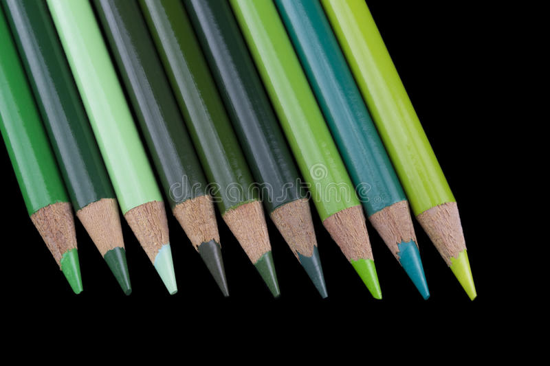 9 Green Pencils - Black Background. Nine green pencils of various hues and shades, lined up and isolated against a dark black background royalty free stock photos