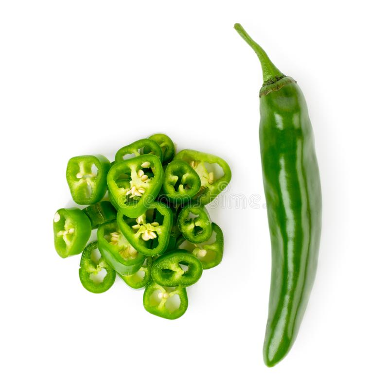 Green pepper and a bunch of sliced pieces on a white background. The view from top. royalty free stock photography