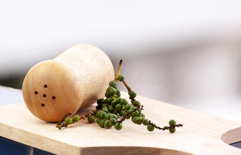 Green pepper and ground pepper. In wood bottle royalty free stock photo
