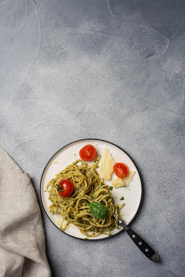 Green pesto spaghetti with tomatoes at plate stock photo