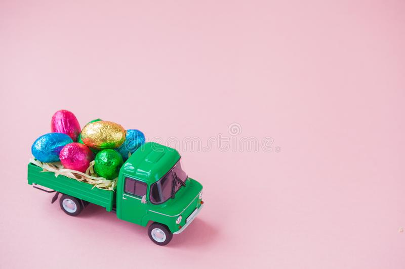Green pickup toy carrying Easter Egg chocolates.  stock photos