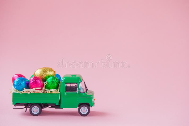 Green pickup toy carrying Easter Egg chocolates.  stock photography