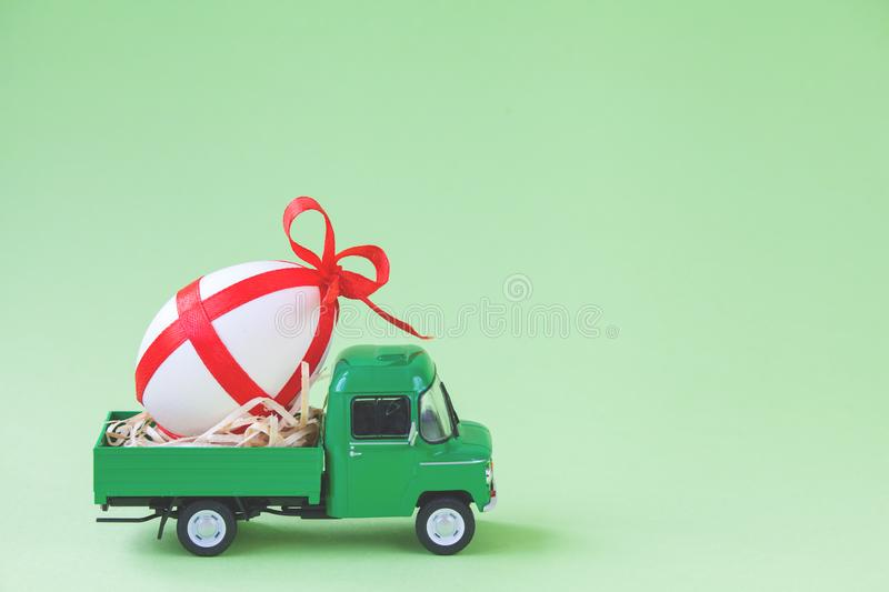 Green pickup toy carrying one decorated easter egg.  stock images