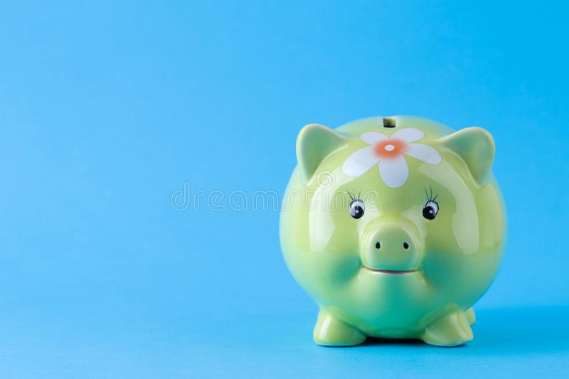 Green pig money box on a bright blue background. Finance, savings, money. space for text royalty free stock image