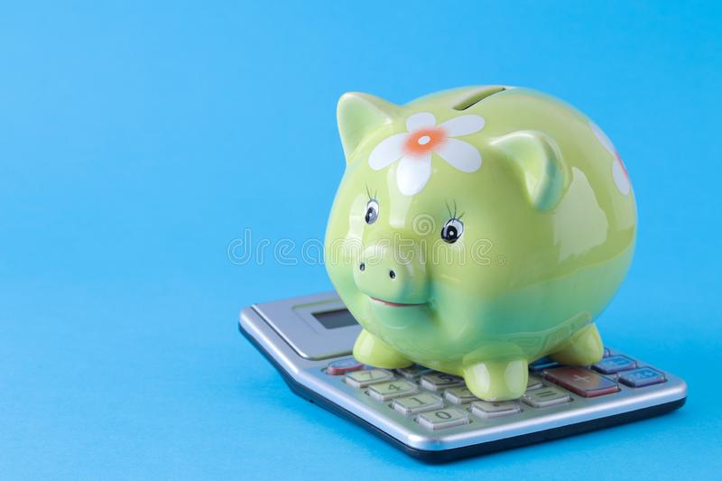 Green pig moneybox and calculator on bright blue background. Finance, savings, money. space for text stock photography