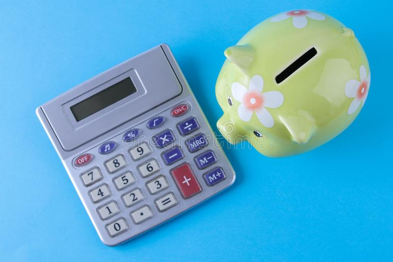 Green pig moneybox and calculator on bright blue background. Finance, savings, money. top view stock photo