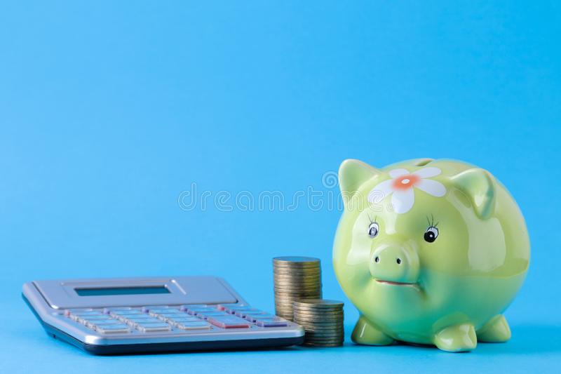 Green pig moneybox and calculator and money on a bright blue background. Finance, savings, money. space for text royalty free stock photo