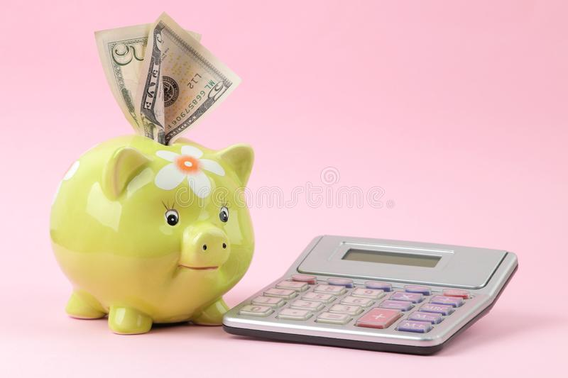 Green pig moneybox and calculator and money on a bright pink background. Finance, savings, money. place for text royalty free stock photo