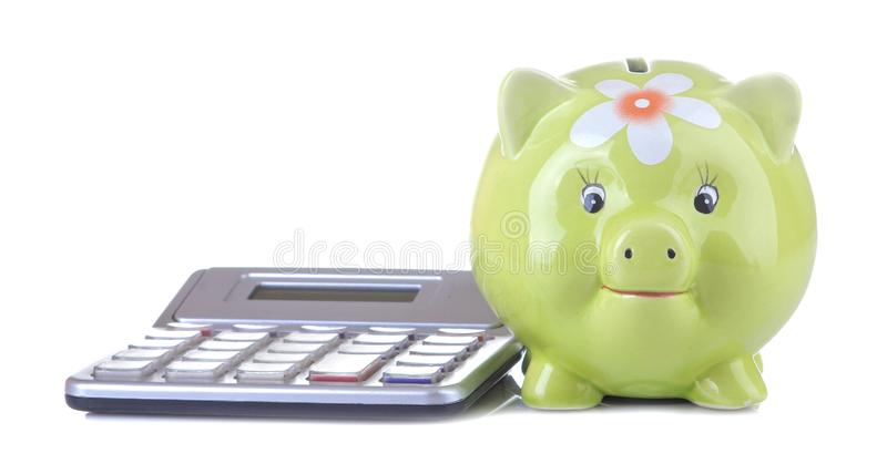 Green pig moneybox and calculator on white isolated background. Finance, savings, money. Green pig moneybox and calculator on white isolated background.  Finance stock photo