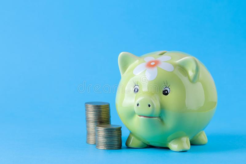 Green pig moneybox and money on bright blue background. Finance, savings, money. space for text. Green pig moneybox and money on bright blue background. Finance stock photo