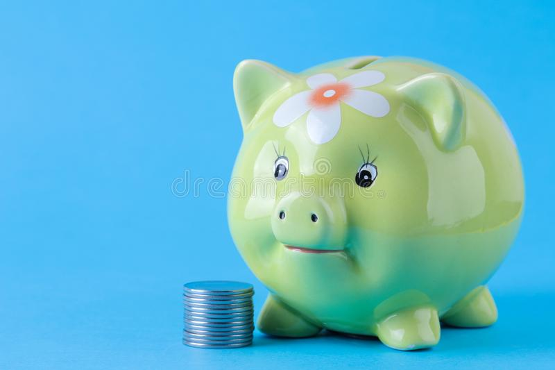 Green pig moneybox and money on bright blue background. Finance, savings, money. space for text. Green pig moneybox and money on bright blue background.  Finance stock photography