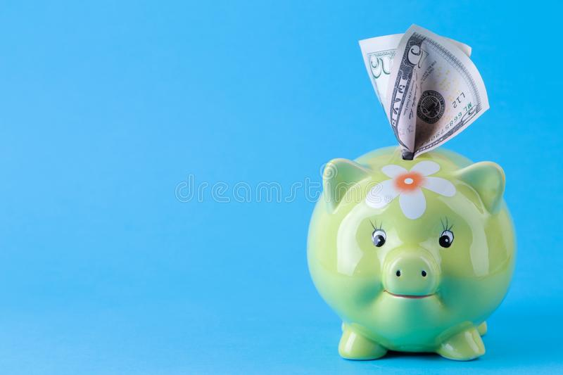 Green pig moneybox and money on bright blue background. Finance, savings, money. space for tex. Green pig moneybox and money on bright blue background. Finance stock photography