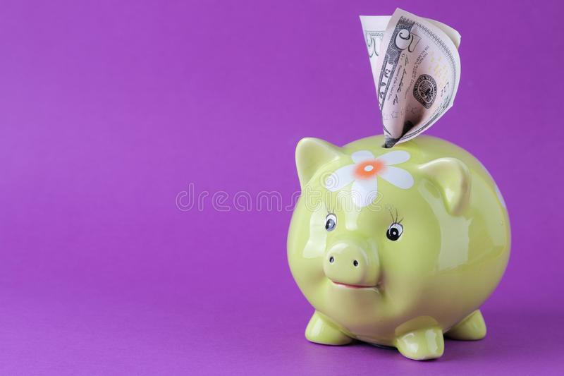Green pig moneybox and money on a bright lilac background. Finance, savings, money. space for text royalty free stock photography