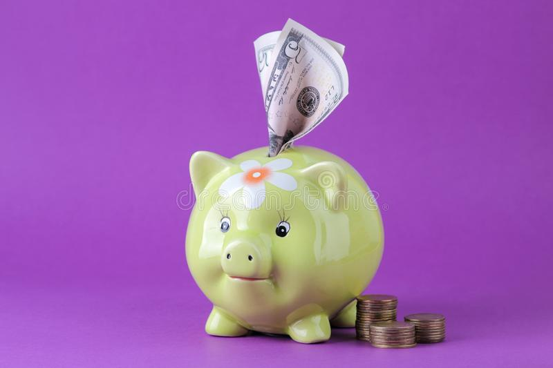 Green pig moneybox and money on a bright lilac background. Finance, savings, money. space for text stock photography