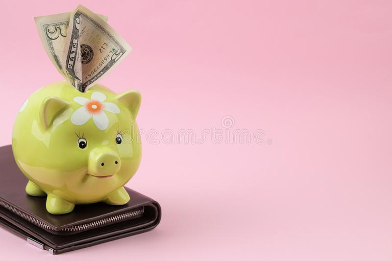 Green pig moneybox and wallet and money on a bright pink background. Finance, savings, money. place for text royalty free stock photo