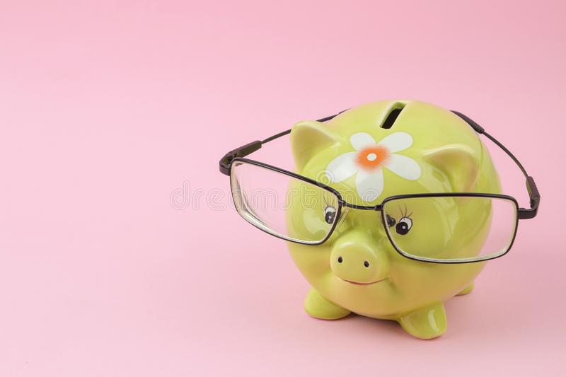 Green piggy bank with glasses on a bright pink background. Finance, savings, money. place for text stock images