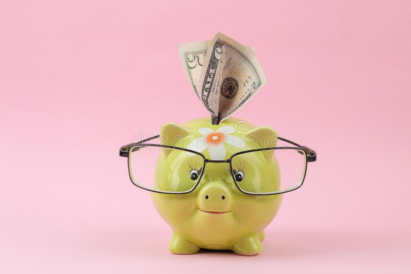Green piggy bank with glasses and money on a bright pink background. Finance, savings, money stock image