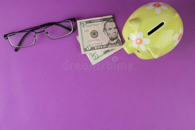 Green piggy bank and money and glasses on a bright purple background. Finance, savings, money. place for text. top view royalty free stock photos