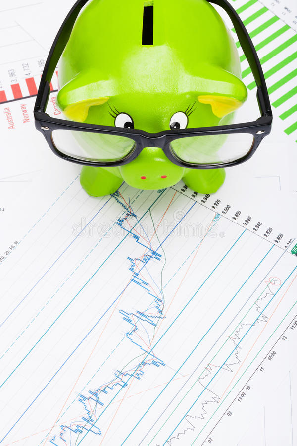 Green piggy bank over stock market chart - view from top. Green piggy bank over stock market chart stock photo