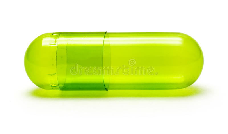 Green Pill. Macro of a green, transparent pill isolated on white royalty free stock photo