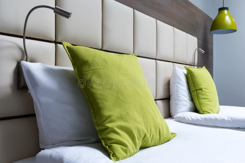 Green pillow, reading lamps and leather bed headboard in modern royalty free stock images