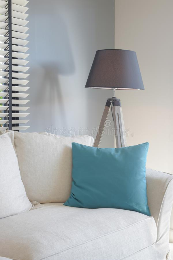 Green pillow on white sofa and black shade standing lamp. In background royalty free stock photography