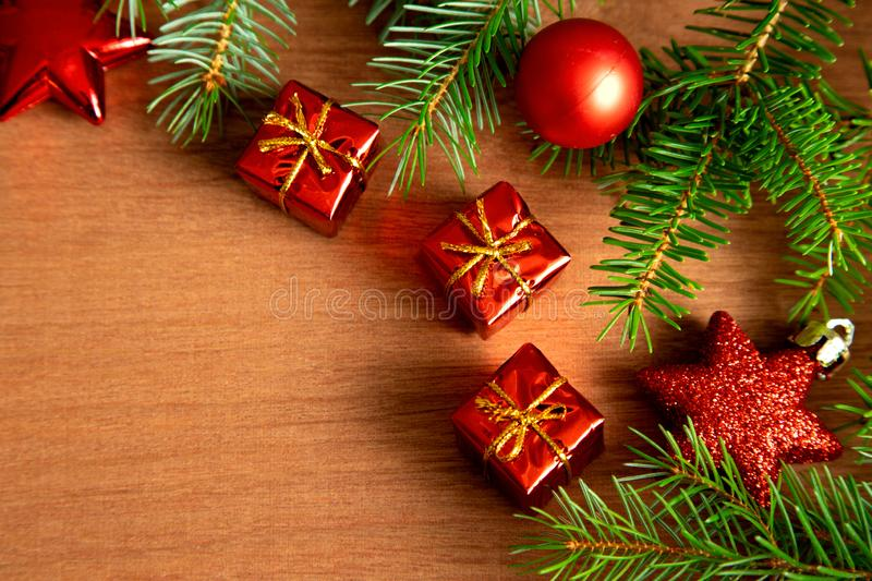 Green pine branches along with Christmas decorations, a red ball and a star and red gift boxes with golden ribbons lie on a wooden royalty free stock photo