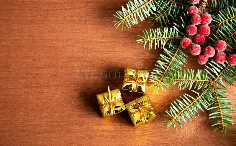Green pine branches and red iced berries on a wooden table with small boxes of gifts in a golden wrapper. Place for text. The stock photo