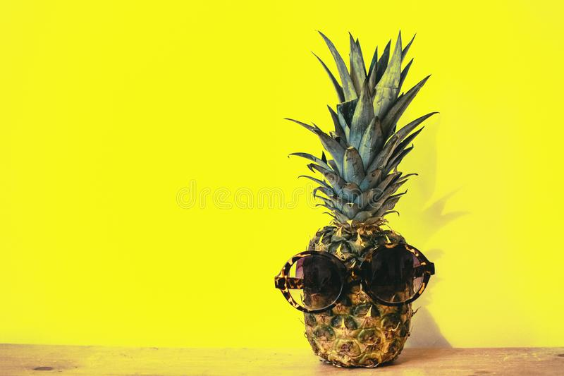 Green Pineapple Fruit With Brown Framed Sunglasses Beside Yellow Surface stock photos