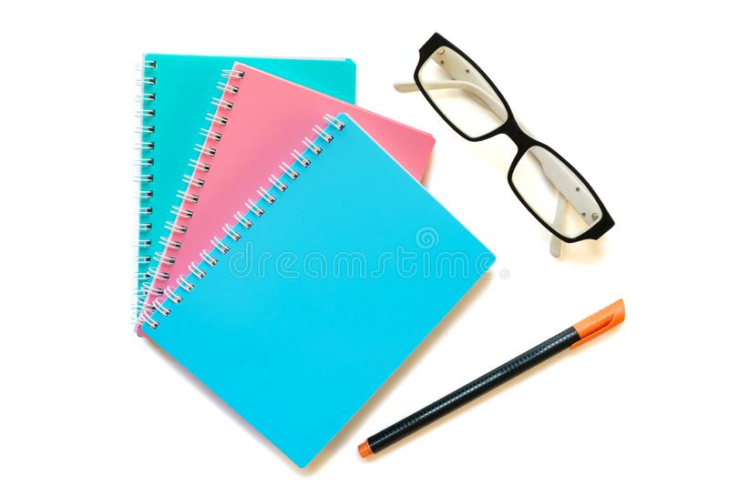 Green pink and blue note book with eye glasses and pen. Photo of Green pink and blue note books with eye glasses and pen royalty free stock image