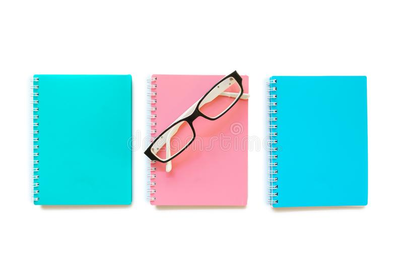 Green pink and blue note books with eye glasses. Photo of Green pink and blue note books with eye glasses stock photos