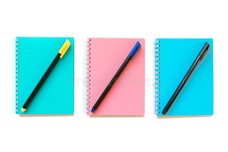 Green pink and blue note books with pens. Photo of Green pink and blue note books with pens royalty free stock images
