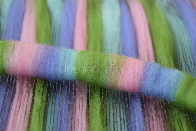 Green, pink, blue, and purple wool rolag on a blending board royalty free stock images