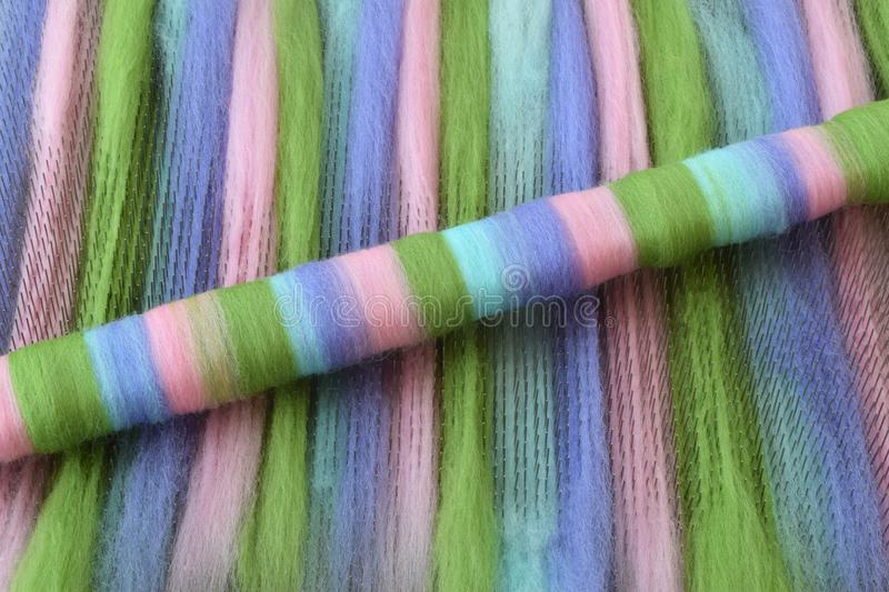 Green, pink, blue, and purple wool rolag on a blending board royalty free stock photography