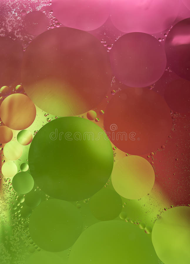 Green,pink Gradient Oil drops in the water -abstract background.  stock image
