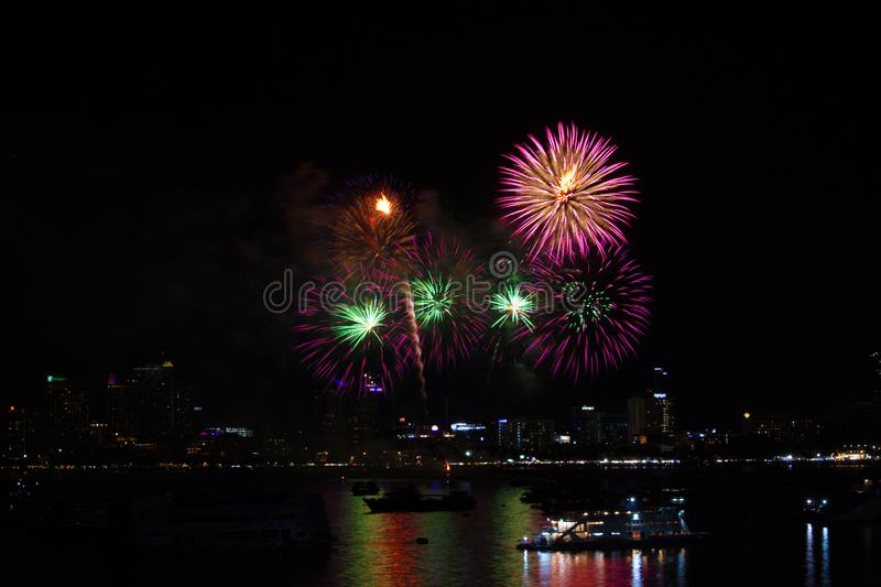 green pink light pink fireworks on beach and reflection color on water surface stock image