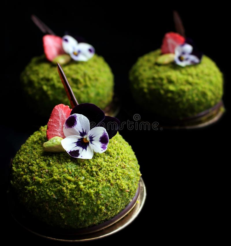 Green pistachio desserts with strawberries and edible flowers royalty free stock image
