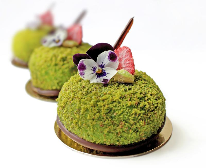 Green desserts with strawberries and edible flowers on golden coasters. Green pistachio desserts with strawberries and edible flowers on golden coasters stock photos
