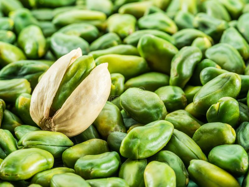 Green pistachio nut with shell over lot of pistachios. royalty free stock photos