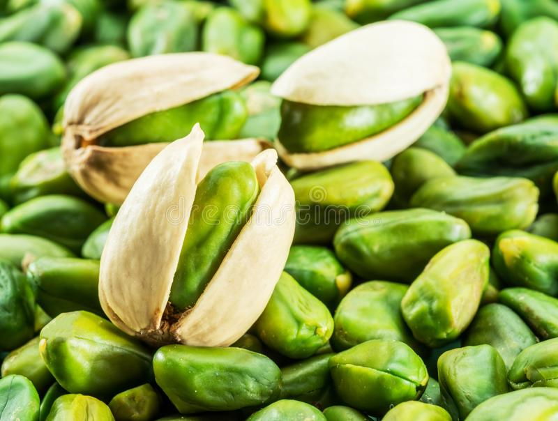 Green pistachio nut with shell over lot of pistachios. royalty free stock images