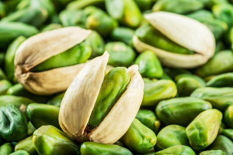 Green pistachio nuts with shell over lot of pistachios. stock photo