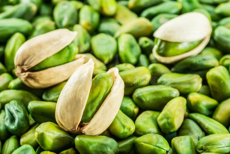 Green pistachio nuts with shell over lot of pistachios. royalty free stock photos